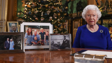The photo used in the Duke and Duchess of Cambridge's Christmas card being displayed on the desk used by the Queen for the recording her annual Christmas Day message.