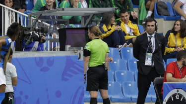 Swiss referee Esther Staubli checks the VAR monitor before awarding Australia's winning goal.