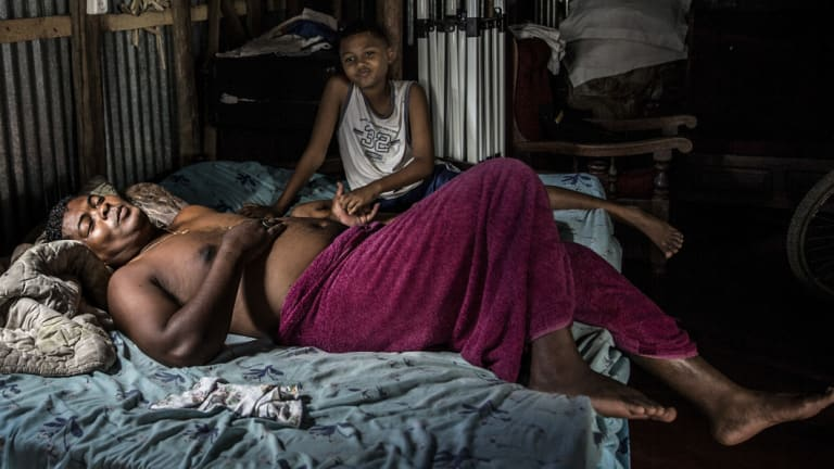 "Pascale Rasafindakoto, a ""commisionnaire"", or middleman, lies at home in bed with his son, in Sambava, Madagascar."