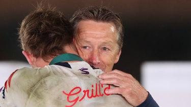 Craig Bellamy embraces Clive Churchill medallist Ryan Papenhuyzen.