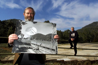 Hamish Lindsay (left) holding one of his own photographs of the former Honeysuckle Creek Tracking Station. Lindsay and John Saxon (right)  worked at the station on the night in 1969 that man first set foot on the moon.