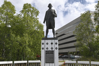 The statue of Captain James Cook stands on a plinth in Resolution Park overlooking the Cook Inlet in Anchorage, Alaska.