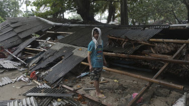A man inspects his house which was damaged by the tsunami in Carita.