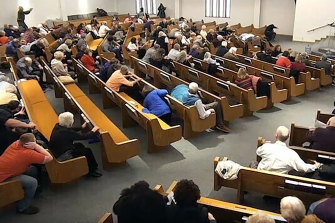 In this still frame from livestreamed video provided by police, churchgoers take cover while a congregant armed with a handgun (top left) engages a man who opened fire (near top centre just right of windows) during a service at West Freeway Church of Christ in White Settlement, Texas.