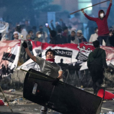 A supporter of Indonesian presidential candidate Prabowo Subianto throws a rock at riot police.
