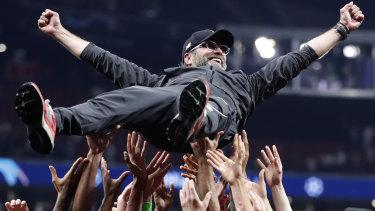 Riding high: Liverpool player lift Jurgen Klopp skywards after their 2-0 win.