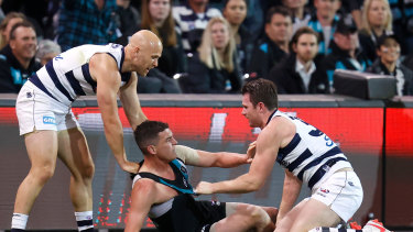 Port's Tom Rockliff is brought down by Patrick Dangerfield and Gary Ablett.