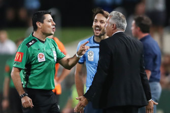 A heated exchange between referee Alireza Faghani, Milos Ninkovic and coach Steve Corica.