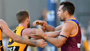 Battle of the ages: Veteran Luke Hodge takes on Hawthorn's Tom Mitchell.