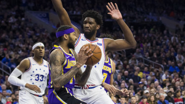 The Lakers' Brandon Ingram (left) is confronted by the 76ers' Joel Embiid.