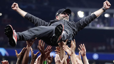 Riding high: Liverpool player lift Jurgen Klopp skywards after their 2-0 win.