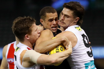 Carlton's Ed Curnow is wrapped up by Jack Billings and Jack Steele.