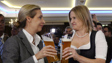 Alice Weidel, left, and Katrin Ebner-Steiner toast with beer at the election party of the Alternative for Germany, AfD, in Mamming, southern Germany, on Sunday.