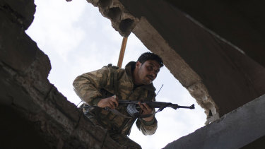 A US-backed Syrian Democratic Forces (SDF) fighter enters a building as fight against Islamic State militants continues in the village of Baghouz, Syria, on Saturday.