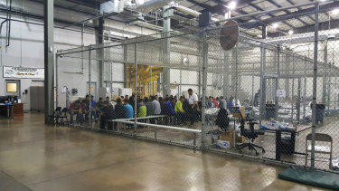 People taken into custody related to cases of illegal entry into the US sit in one of the cages at a facility in McAllen, Texas.