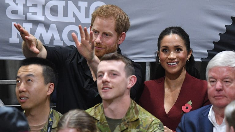 Prince Harry and Meghan watch basketball in a wheelchair.