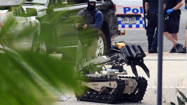 A police bomb squad robot is deployed at the Coronation Drive siege.