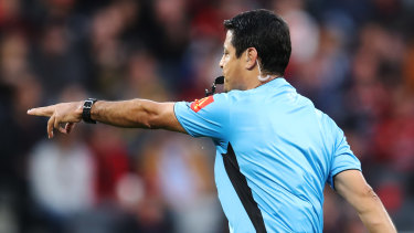 Referee, Alireza Faghani points to the penalty spot after reviewing a hand-ball with VAR.