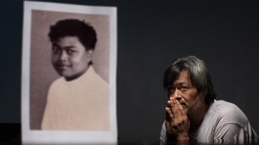 Mark Apuron, 45, sits beside a photo of himself when he was 15 years old, the age when he says he was raped by his uncle, former Archbishop Anthony Apuron, in Guam.