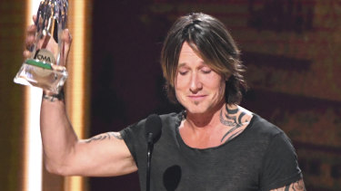 Keith Urban accepts the award for entertainer of the year at the 52nd annual CMA Awards.