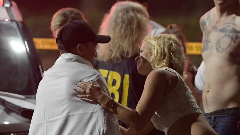 People comfort each other as they stand near the scene in Thousand Oaks, California.