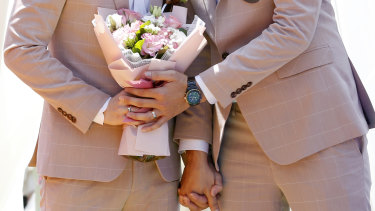 A married couple holds a bouquet during a pro same-sex marriage party.