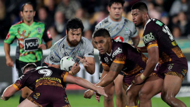 The wall: The Brisbane defence crowds out the Warriors' Peta Hiku.