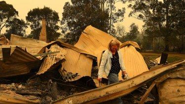 Averil Berryman walks through the ruins of her business in Mogo's Main Street that was destroyed by the fire that swept through the town.