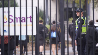 A police officer at the gates of Victoria University Secondary College in St Albans on Wednesday morning.