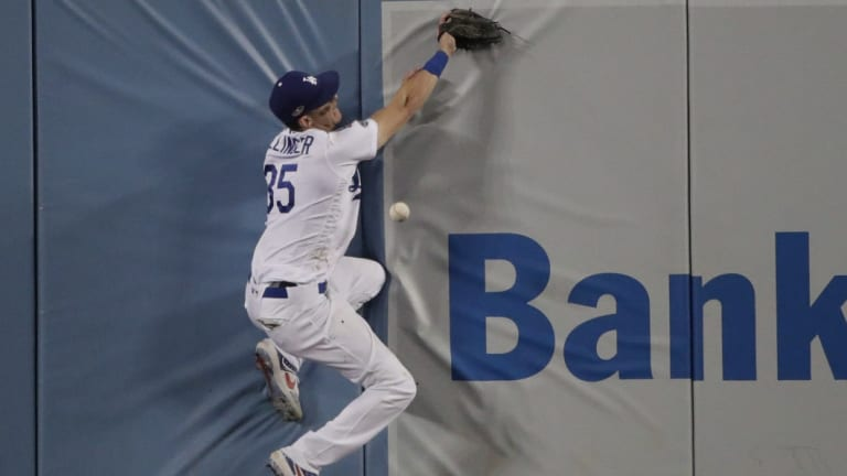 Cody Bellinger crashes into the wall in centre field as he attempts a catch against the Brewers.
