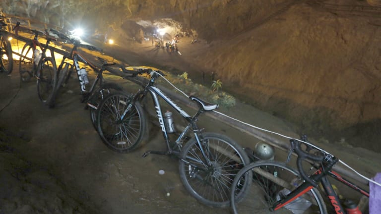Bicycles left by a group of missing boys lean against a railing at the entrance of a deep cave in Chiang Rai, northern Thailand.