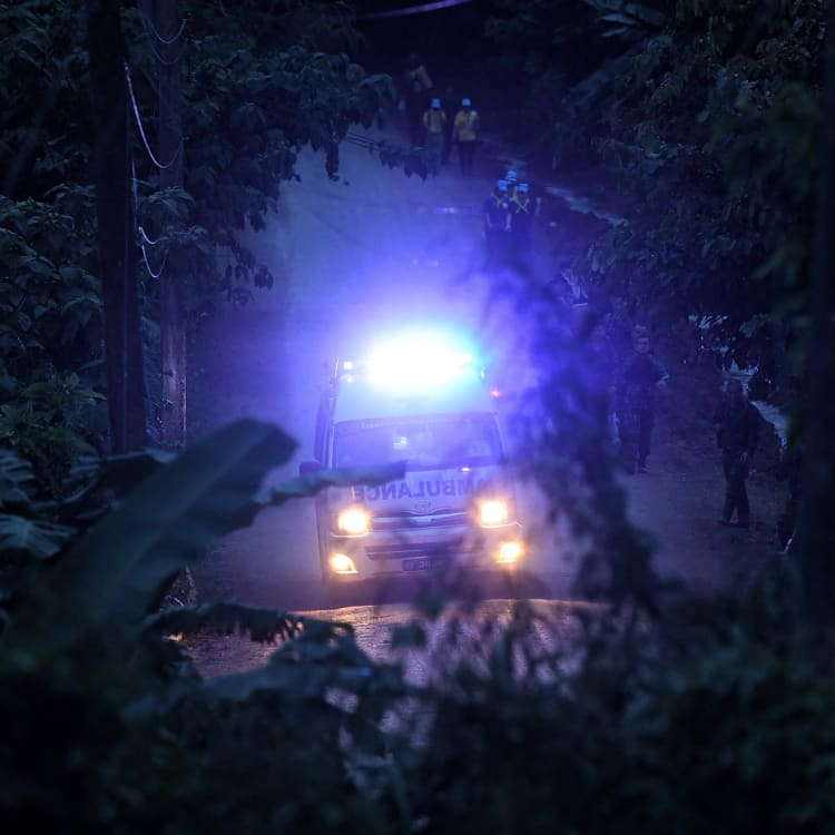 An ambulance races through the forest with one of the rescued boys on board.