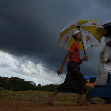 Storm clouds hang overhead as a Rohingya boys carrying umbrellas walk on a main road in Kutupalong camp.