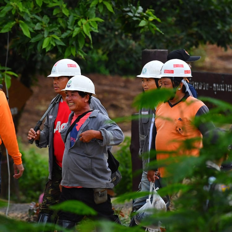 All smiles: Rescue workers cannot contain their happiness at the success of the operation.