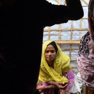 A Rohingya woman sits outside her shelter.