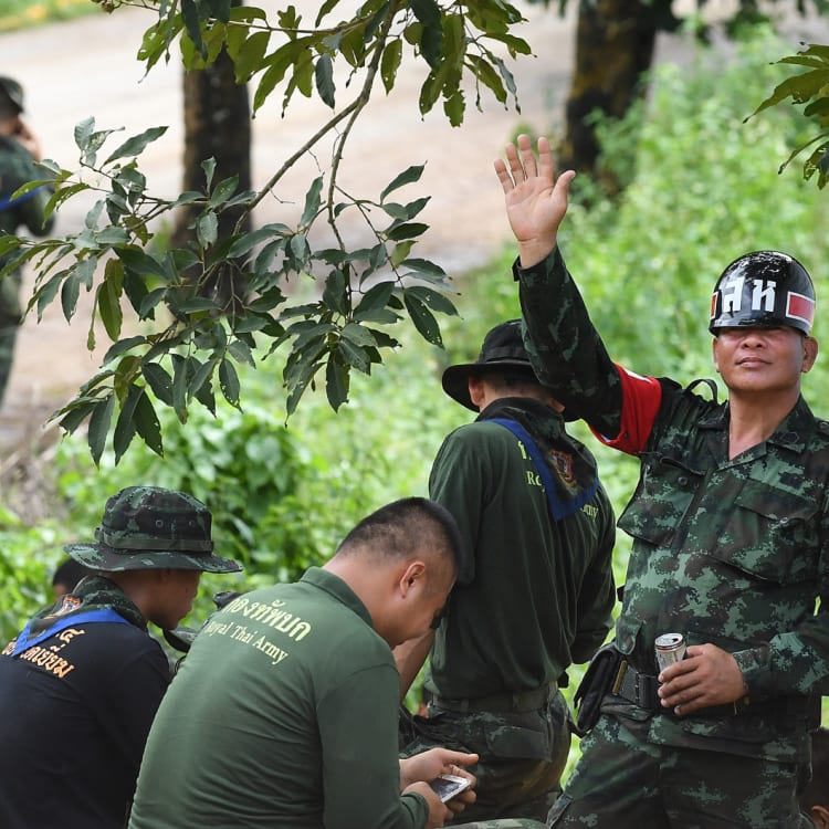 A Thai military policeman holds up five fingers to indicate the number of people rescued from the cave.
