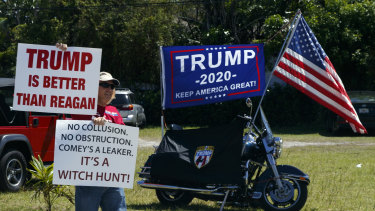 A supporter of US President Donald Trump awaits his motorcade in West Palm Beach, Florida, on Saturday.