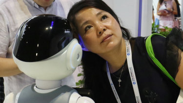 A woman listens to what a robot responds to her at the World Robot Conference.