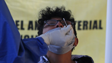 A man gets a nasal swab for a rapid COVID-19 test at a post set up in Mexico City.