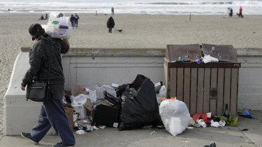A woman walks past rubbish piled next to a garbage bin at Ocean Beach in San Francisco last week.