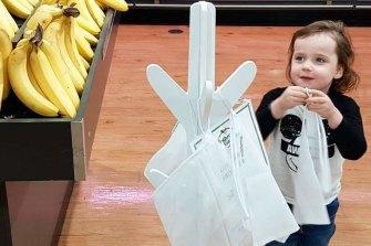 Charlie Barns, 4, refills the reusable produce bag station.