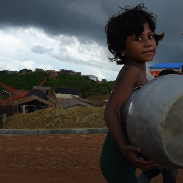 Storm clouds hang overhead as a Rohingya child carries a pot in Kutupalong camp.