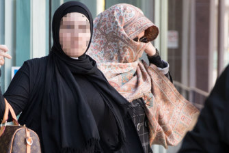 Lubna Al-Hashimy, right, covers her face with a scarf after being arrested over the alleged fraud. She is pictured leaving Bankstown police station with a supporter who has not been charged with any offences.