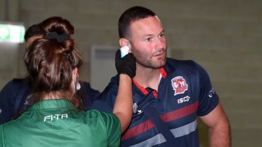 Roosters captain Boyd Cordner has his temperature taken before the clash with the Broncos.