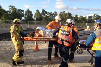 A welder on the North West Metro, injured by a falling boulder, is put on a stretcher.