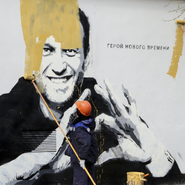 A municipal worker in St Petersburg paints over a mural of imprisoned opposition leader Alexei Navalny, in April.