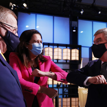 The president of the International Olympic Committee, Thomas Bach, right, bumps elbows with Premier Annastacia Palaszczuk and John Coates.