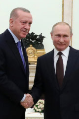Russian President Vladimir Putin, right, and Turkish President Recep Tayyip Erdogan shake hands during their meeting at the Kremlin in Moscow, Russia.