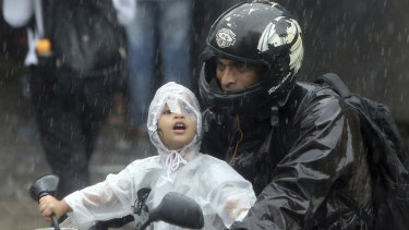 A boy rides a bike wrapped in a raincoat in Mumbai, India, where a building has collapsed.