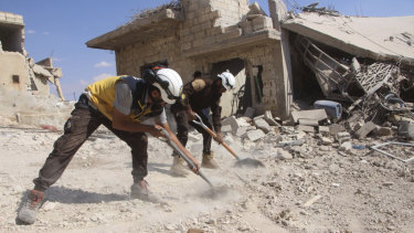 Volunteer rescuers clean rubble from a house damaged by a Syrian government air strike in Hobeit , near Idlib.